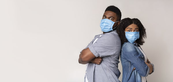 Young Couple Wearing Protective Medical Masks And Standing Back To Back With Scared Face Expression
