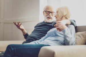 Older couple talking happily on their couch